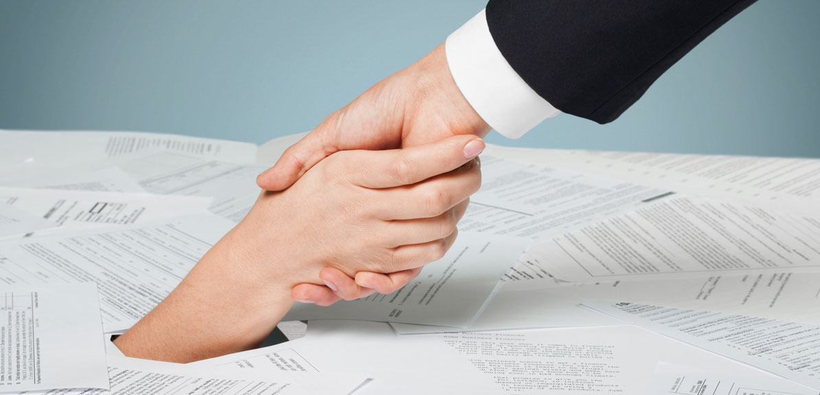 man holding a womans hand pulling her from a pile of paperwork